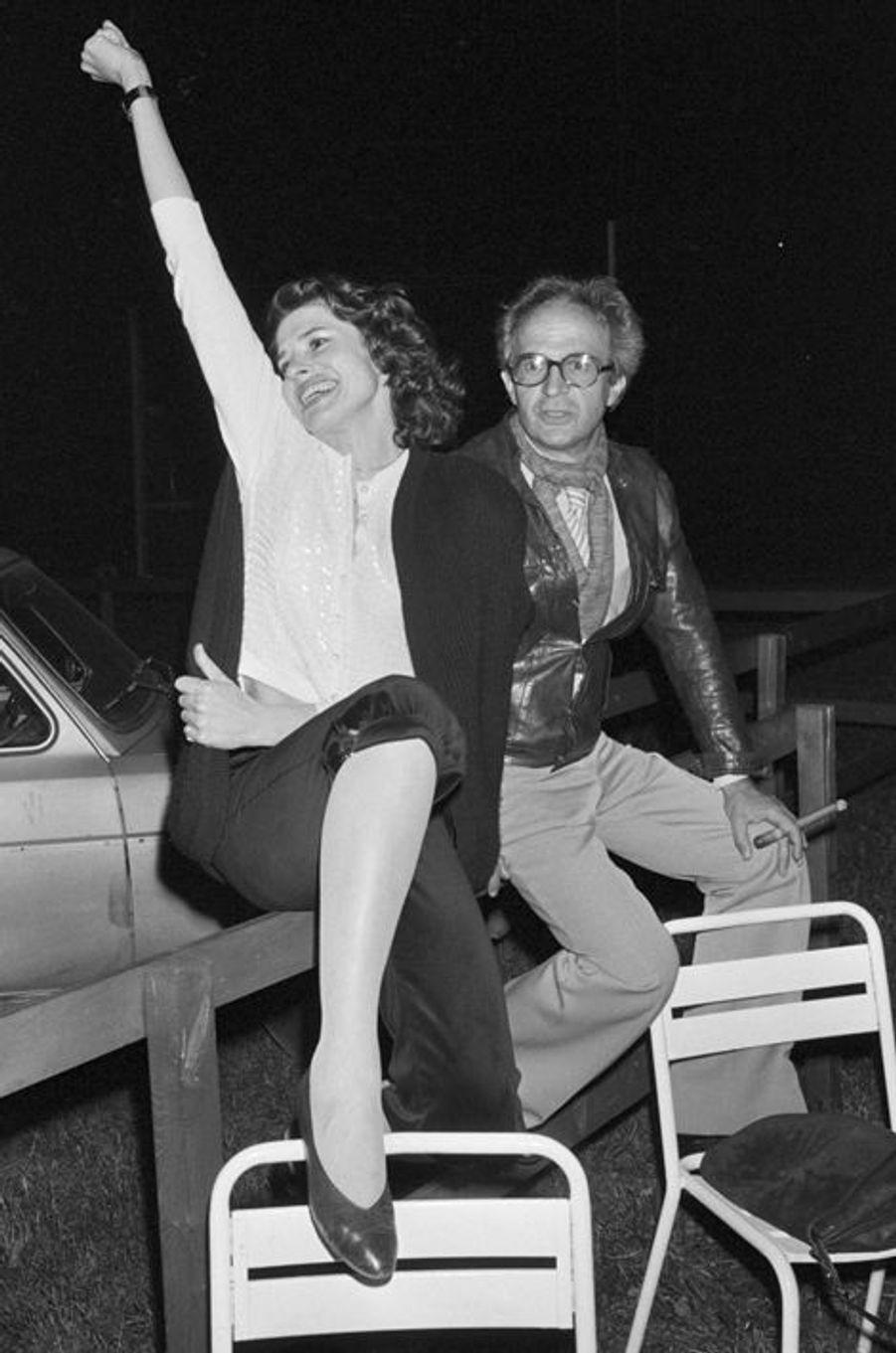 """France, Grenoble, 8 mai 1981, pendant le tournage du film """"La femme d'à côté"""", lors d'une soirée de repos, le réalisateur François TRUFFAUT est assis sur une barrière de bois près de l'actrice Fanny ARDANT, à l'époque sa compagne. Elle sourit en tendant un bras en l'air, une jambe sur une chaise en métal posée devant elle. Lui tient un cigare dans une main. Derrière eux, une voiture garée."""