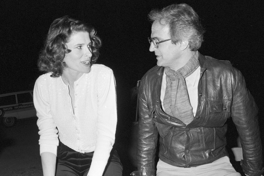 """France, Grenoble, 8 mai 1981, pendant le tournage du film """"La femme d'à côté"""", lors d'une soirée de repos, le réalisateur François TRUFFAUT est assis sur une barrière de bois près de l'actrice Fanny ARDANT, à l'époque sa compagne. Ils se regardent. Derrière eux, des voitures garées."""