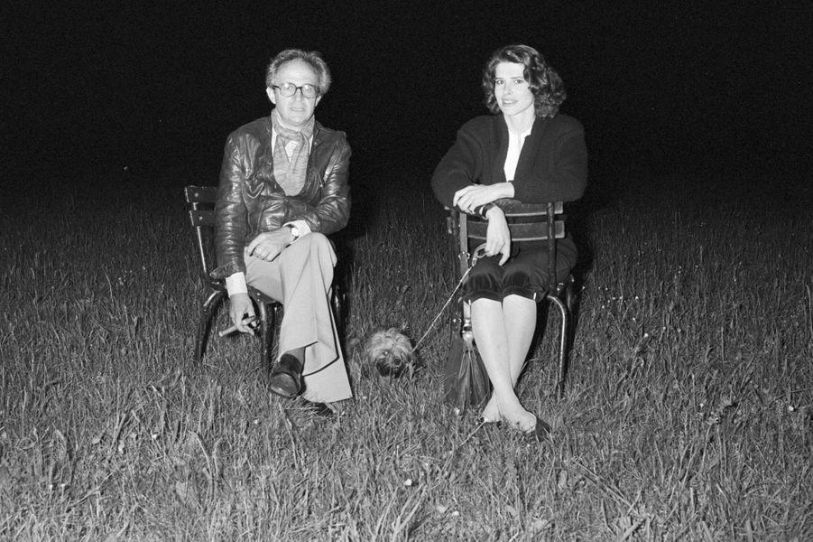"""France, Grenoble, 8 mai 1981, pendant le tournage du film """"La femme d'à côté"""", lors d'une soirée de repos, le réalisateur François TRUFFAUT est assis sur une chaise près de l'actrice Fanny ARDANT, à l'époque sa compagne. Elle tient en laisse son chien Golaud, un bichon havanais, qui est couché entre les 2 chaises. François tient un cigare à la main, le couple fixe l'objectif."""