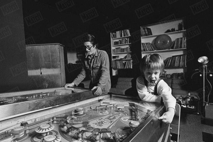 Jacques Dutronc et son fils Thomas (2 ans et demi) jouent au flipper, dans leur maison du XIVème arrondissement de Paris, en janvier 1976.