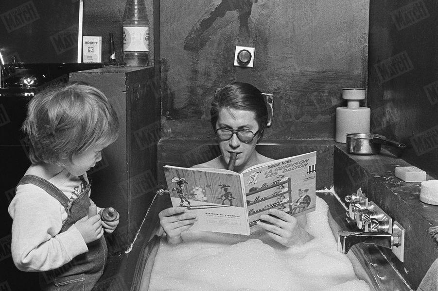 Jacques Dutronc prend son bain, cigare aux lèvres et Lucky Luke dans les mains, sous le regard de son fils Thomas (2 ans et demi), dans leur maison du XIVème arrondissement de Paris, en janvier 1976.