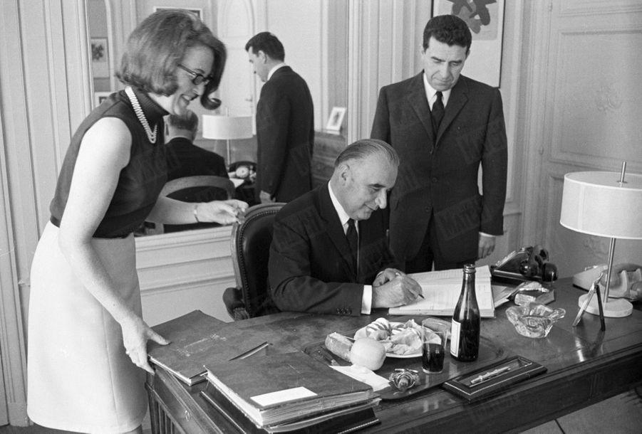 Le candidat Georges Pompidou, dans son bureau de la Tour Maubourg, avec Pierre Juillet et Madeleine Negrel, devant son plateau repas, en mai 1969.