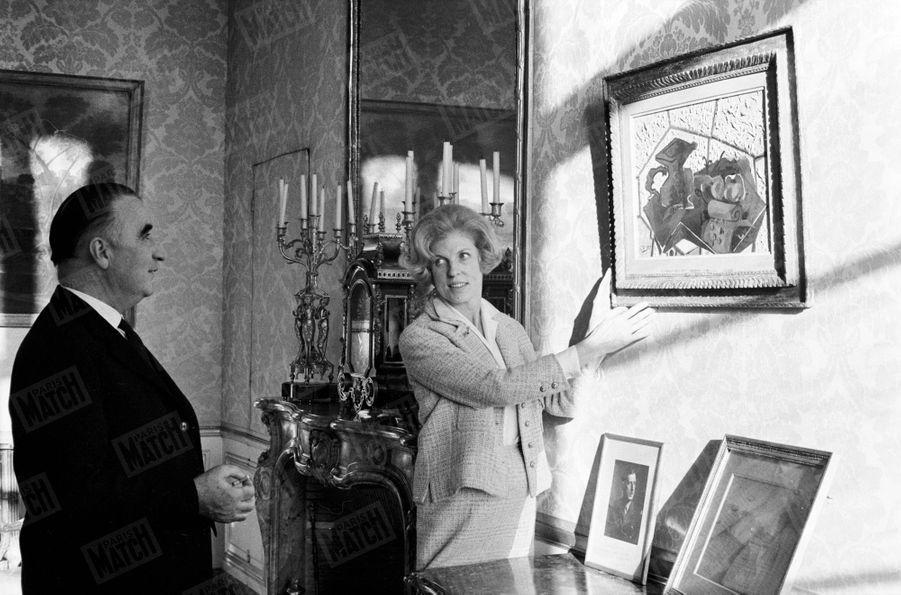 """Le Premier Ministre Georges Pompidou regarde son épouse Claude accrocher le tableau """"Le tapis vert"""" de Georges Braque dans les appartements privés de Matignon, en décembre 1962."""