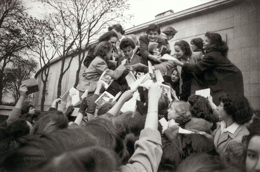 Gérard Philipe signant des autographes à ses admiratrices, venant d'assister à Chaillot aux matinées du TNP en mai 1954.