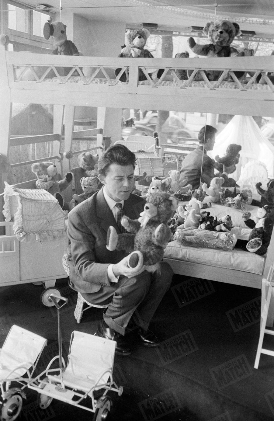 Gérard Philipe choisit un ours en peluche dans un magasin de jouets, au lendemain de la naissance de sa fille le 21 décembre 1954 à la clinique du Belvedère à Boulogne-Billancourt.
