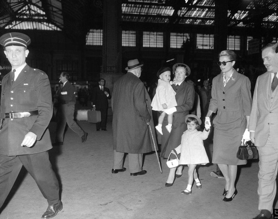 Grace de Monaco tient sa fille Caroline par la main, tandis que le nanny anglaise Mlle King porte le petit Albert, à l'arrivée de la famille à la Gare de Lyon, à Paris, le 5 octobre 1959.