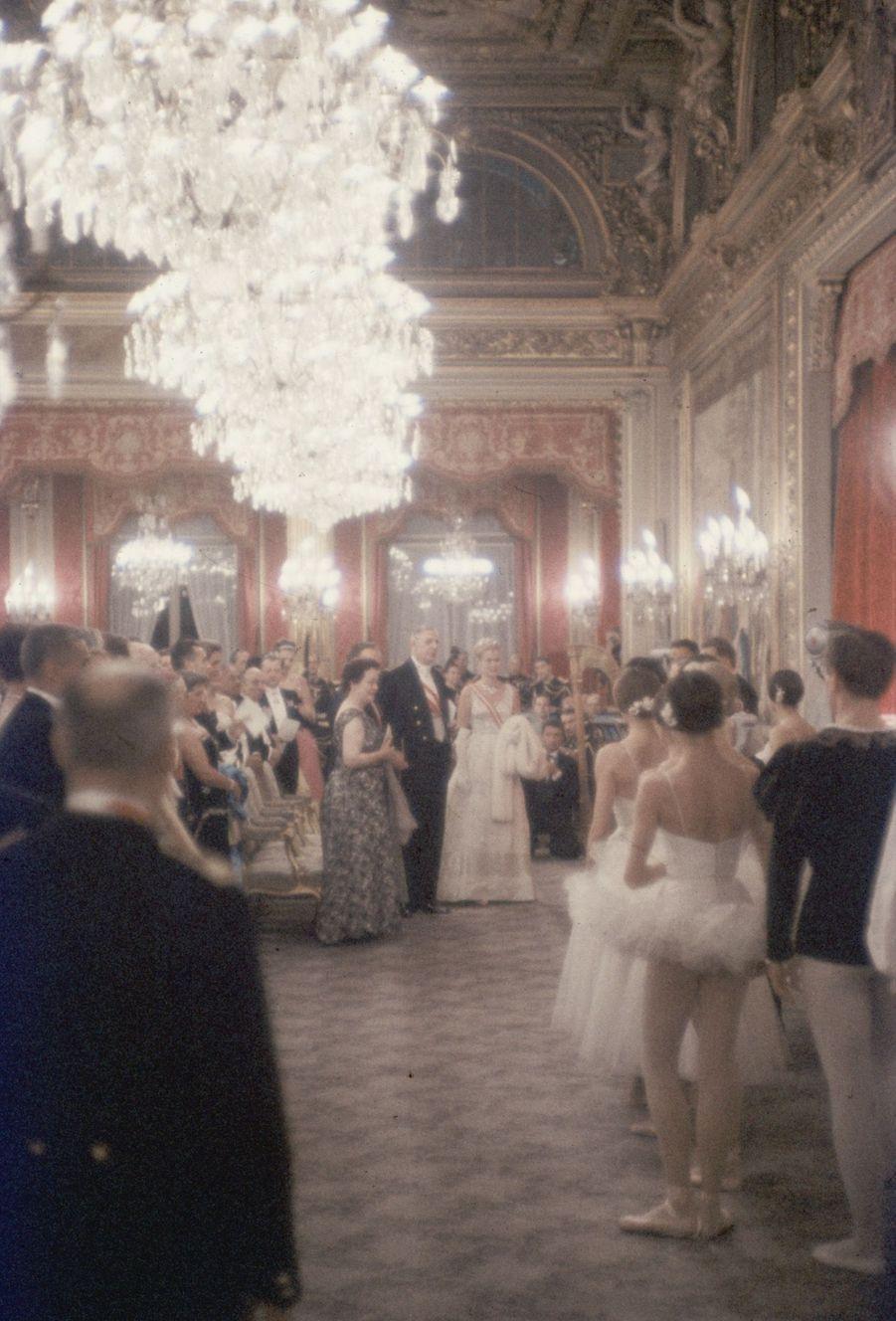"""« Sous les lustres, l'opéra à domicile. Dans la salle des fêtes de l'Élysée, après le dîner de 130 couverts et les toasts traditionnels, c'est l'heure du divertissement. 230 invités sont serrés sur des chaises dorées. Au premier rang Mme de Gaulle, le prince Rainier, le Président et la princesse Grace en robe de satin pailletée de cristal, signée Lanvin; sur la minuscule scène de 5 mètres sur 6, c'est un grand spectacle donné par le corps de ballet de l'Opéra. Au programme : """"Le Clair de Lune """" de Debussy; """"Le Casse-noisette"""" de Tchaikowsky et """"La Suite en blanc """" de Lalo. » - Paris Match n°550, samedi 24 octobre 1959."""