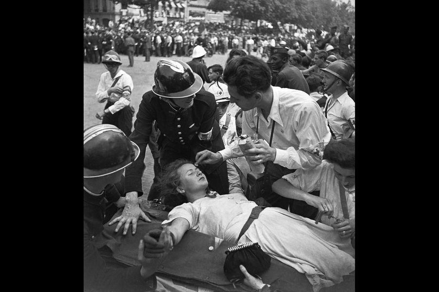 Le 26 août 1944, les volontaires de la Croix Rouge s'occupent d'une jeune femme ayant fait un malaise
