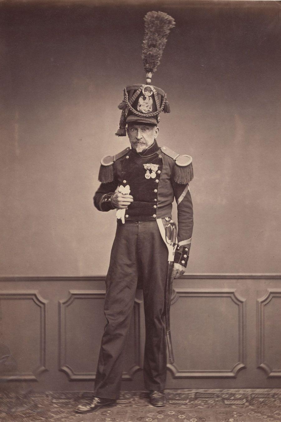 L'officier du génie. Ici, Monsieur Lefebre, du 2ème régiment de génie, porte une tenue d'officier et un shako à plumet orné de l'aigle impéri...