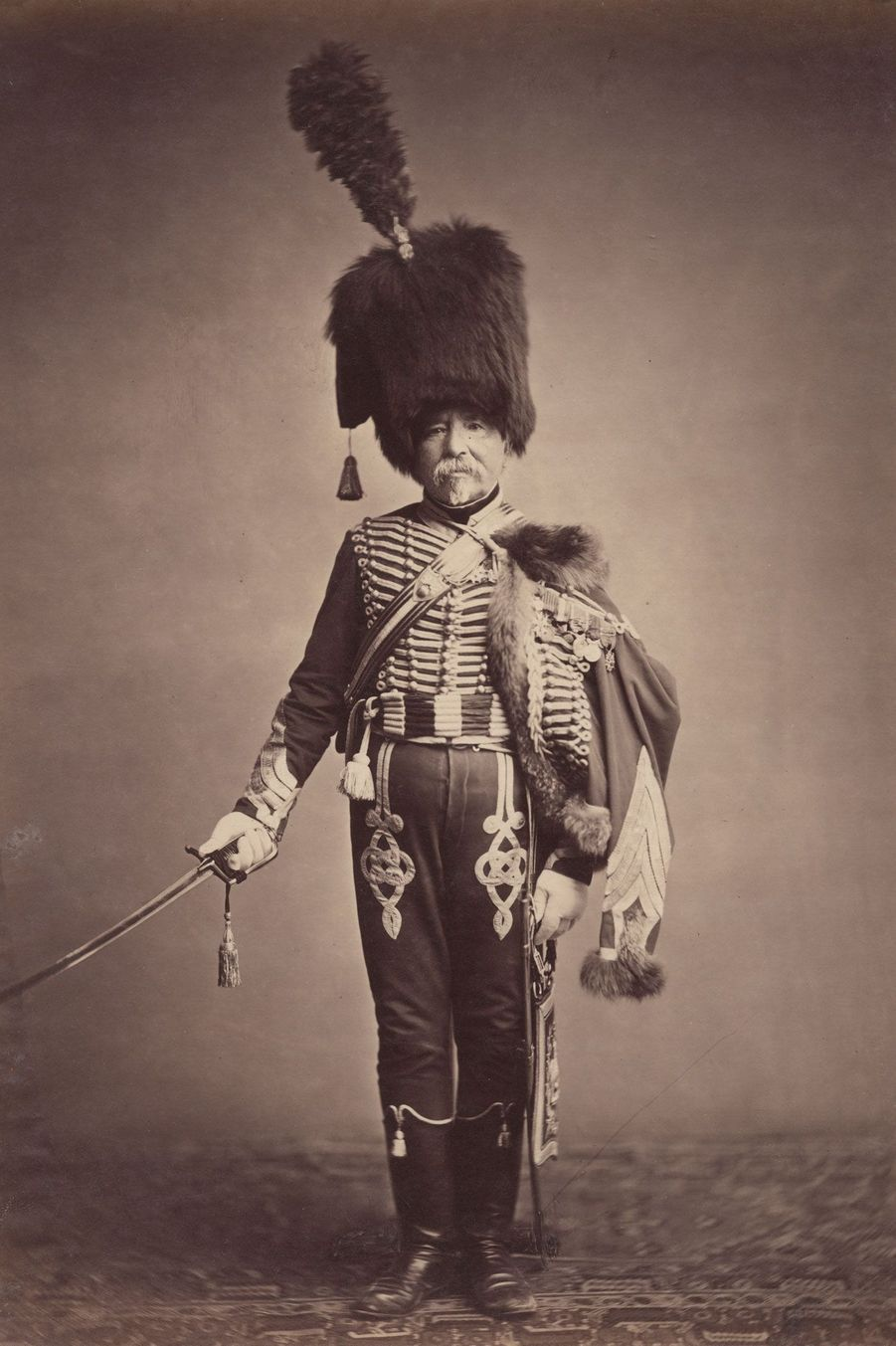 """Le hussard. Monsieur Fabry était un intendant au 1e régiment de hussards. Il porte un couvre-chef d'origine turque, appelé """"colback""""."""