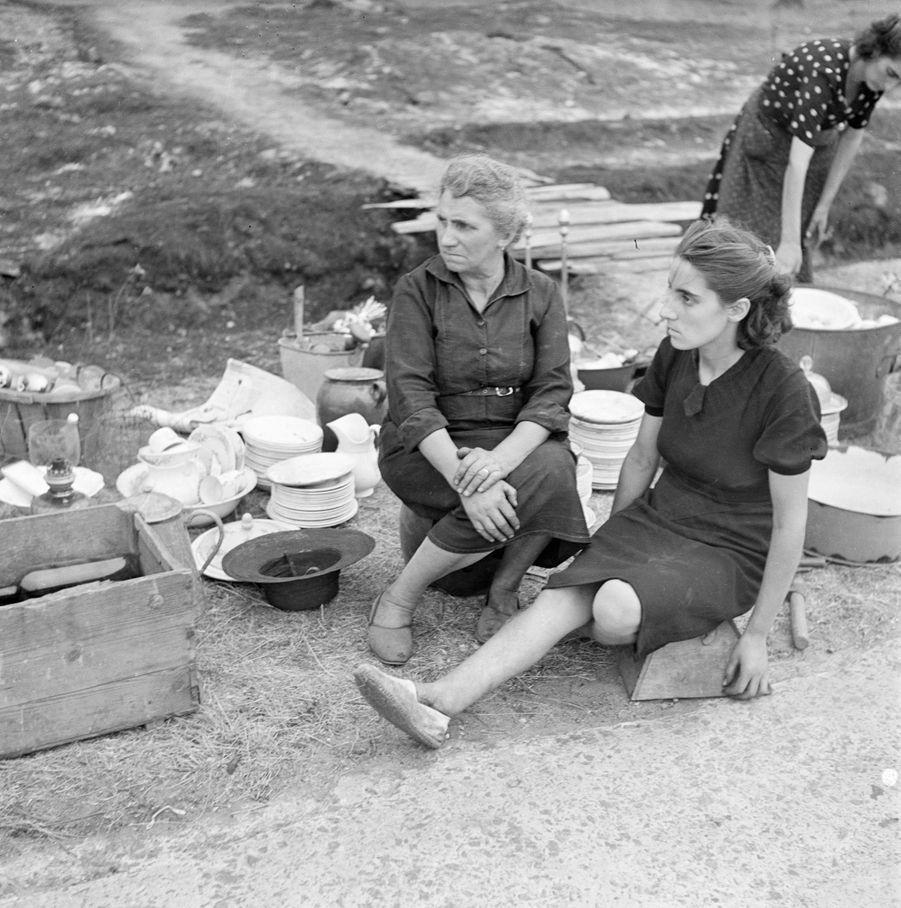 «Sur le bord de la route, Mme Videaux et ses deux filles attendent un camion de secours. Loin de la zone dangereuse, elles veulent rebâtir leur ferme. » - Paris Match n°24, 3 septembre 1949
