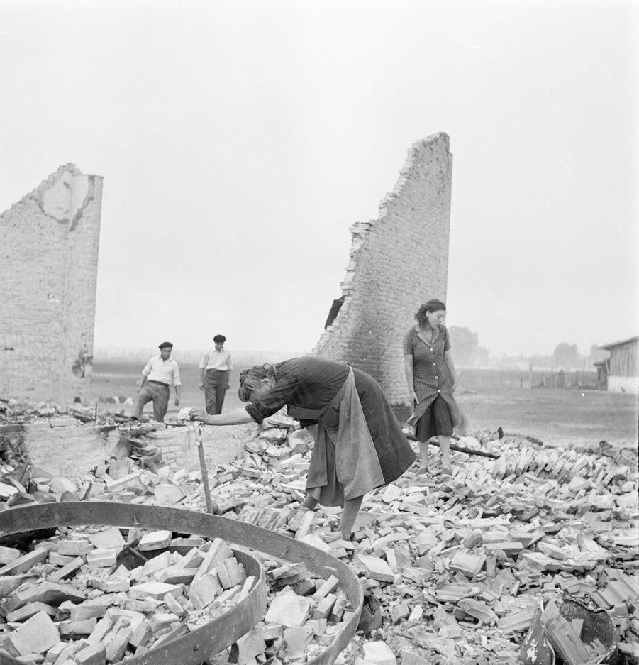 «Dans les ruines de leur maison, ces victimes du sinistre recherchent passionnément un souvenir du bonheur perdu. Cette ferme, au lieu-dit Saint-Jacques, a brûlé en une heure. Il ne reste que des débris, des cendres, des cadavres d'animaux. Demain, le travail reprendra pour reconstruire.» - Paris Match n°24, 3 septembre 1949