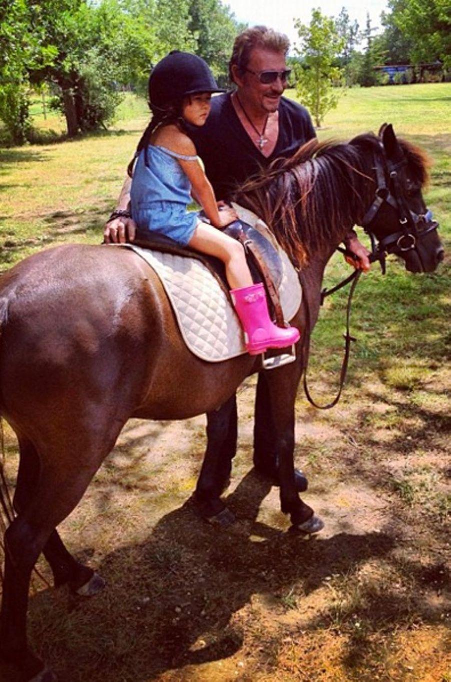 Johnny Hallyday guide sa petite fille sur un cheval