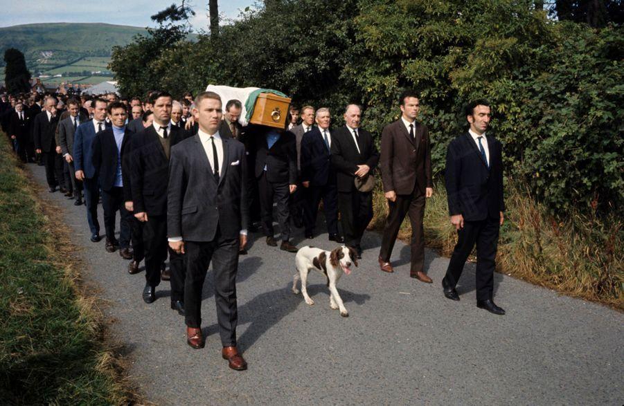 """«L'enterrement du receveur d'autobus Samuel Mac Larnon, 30 ans. Des milliers d'hommes, le chien Tobby, pas une femme : le drapeau vert, blanc et orange : les catholiques ont repris pour lui traditions et symboles du nationalisme irlandais. Samuel est tué, le 15 août, par une balle tirée d'une automitrailleuse des """"Spéciaux B"""" » - Paris Match n°1060, 30 août 1969"""