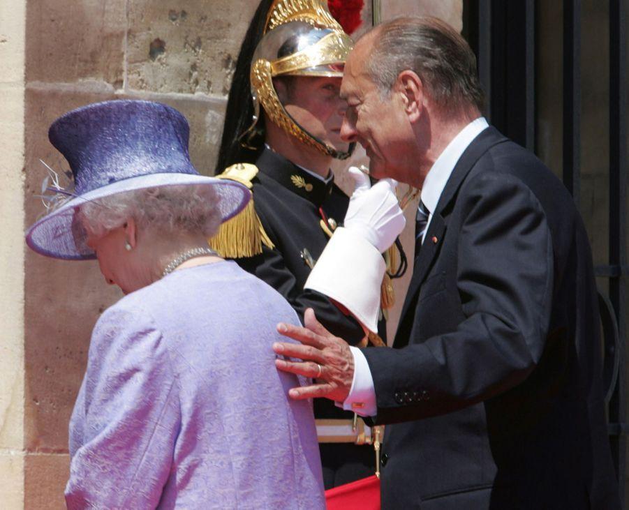 Jacques Chirac avec la reine Elizabeth II à Caen, lors des célébrations du 60e anniversaire du Débarquement en juin 2004. En touchant légèrement le dos de la reine, un geste interdit par le protocole, le président français avait scandalisé les tabloïds britanniques...