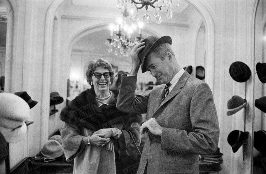 James Stewart essaie des chapeaux sous le regard amusé de son épouse Gloria, lors d'un passage à Paris en novembre 1959.