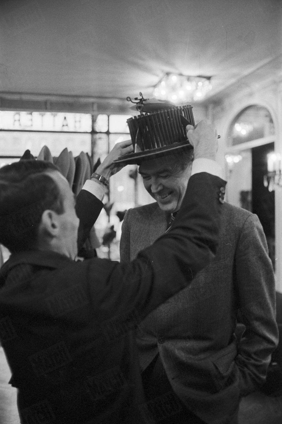 James Stewartportant l'appareil à mesurer le tour de tête chez un chapelier, lors d'un passage à Paris en novembre 1959.