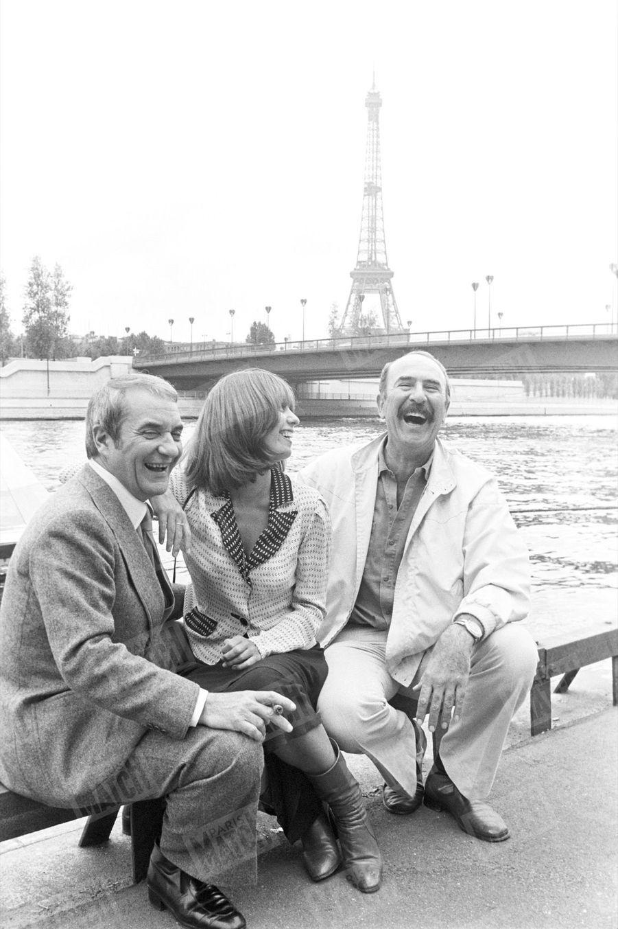 Jean-Pierre Marielle avec Caroline Cartier et Jean Carmet, ses partenaires à l'écran dans « Plus ça va, moins ça va », de Michel Vianey, le 14 août 1977.