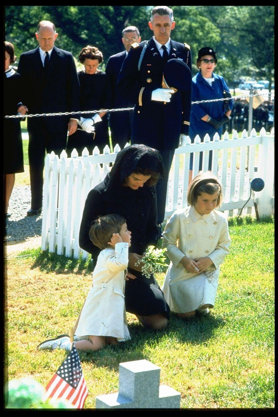 Jacqueline Kennedy et ses enfants John Jr. et Caroline prient sur la tombe du président assassiné, le jour de son premier anniversaire après sa mort, le 29 mai 1964.