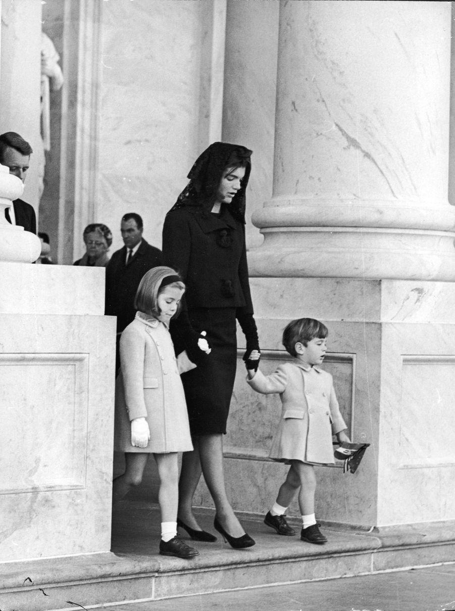 Le 26 novembre 1963, la Première dame Jacqueline Kennedy tient les mains de ses deux enfants, John Jr et Caroline, alors qu'ils quittent la Maison Blanche pour se rendre à la chapelle ardente du président assassiné, John F. Kennedy, au Capitole, Washington