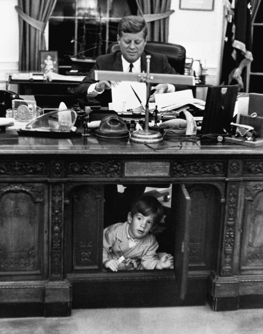 John Jr., âgé de 18 mois, dans le bureau oval de la Maison-Blanche, sous le regard de son père JFK, le 25 mai 1962.