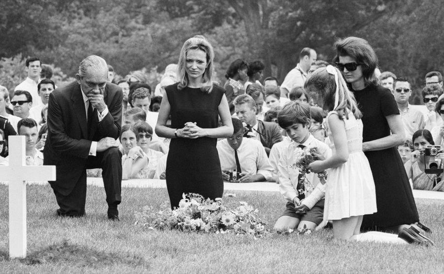 Jackie Kennedy, ses enfants Caroline et John, et Lee Radziwill (la soeur cadette de Jackie), s'agenouillent devant la tombe de Robert F. Kennedy, le 9 juin 1968. Le sénateur a été assassiné trois jours plus tôt, alors qu'il était en campagne pour l'élection présidentielle.