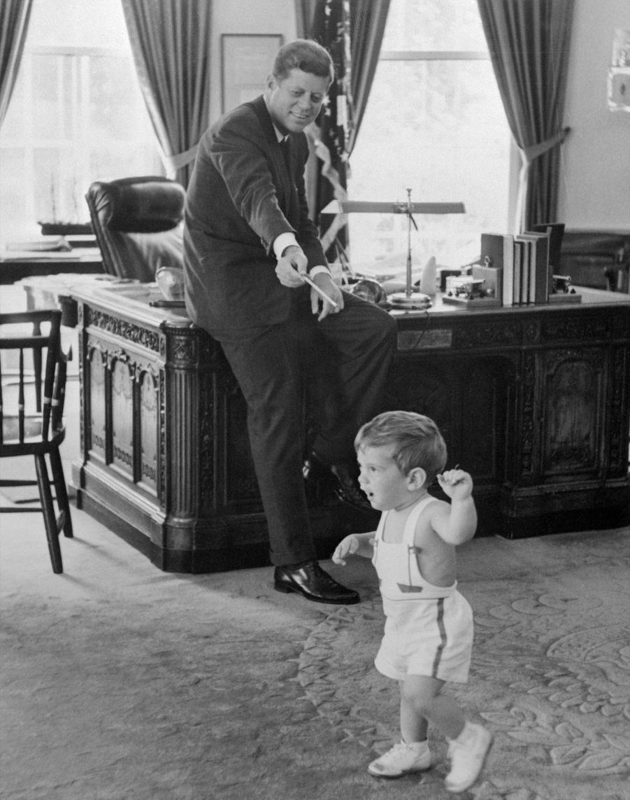 John Jr., âgé de 18 mois, fait ses premiers pas dans le bureau du chef de cabinet de la Maison-Blanche, sous le regard de son père JFK, le 25 mai 1962.