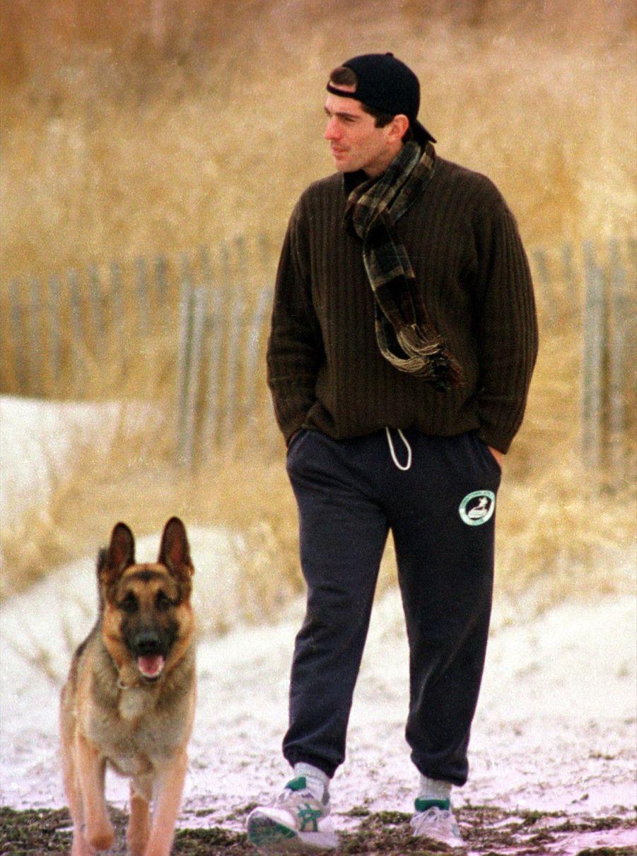 John F. Kennedy Jr., avec son chien le long de la plage de Hyannis Port, dans le Massachusetts, le lendemain du décès de sa grand-mère Rose Kennedy, le 24 janvier 1995.
