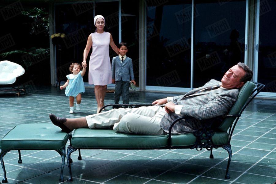 John Wayne chez lui avec son épouse Pilar et leurs deux enfants Ethan et Marisa, à Newport Beach, Californie, en juin 1967.