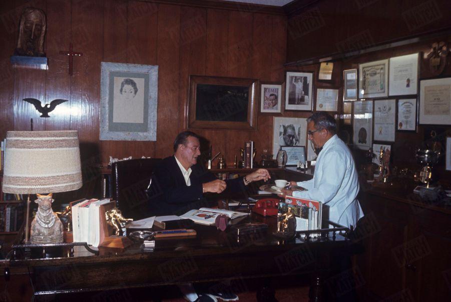 John Wayne dans le bureau de sa villa de Newport Beach, Californie, en juin 1967.