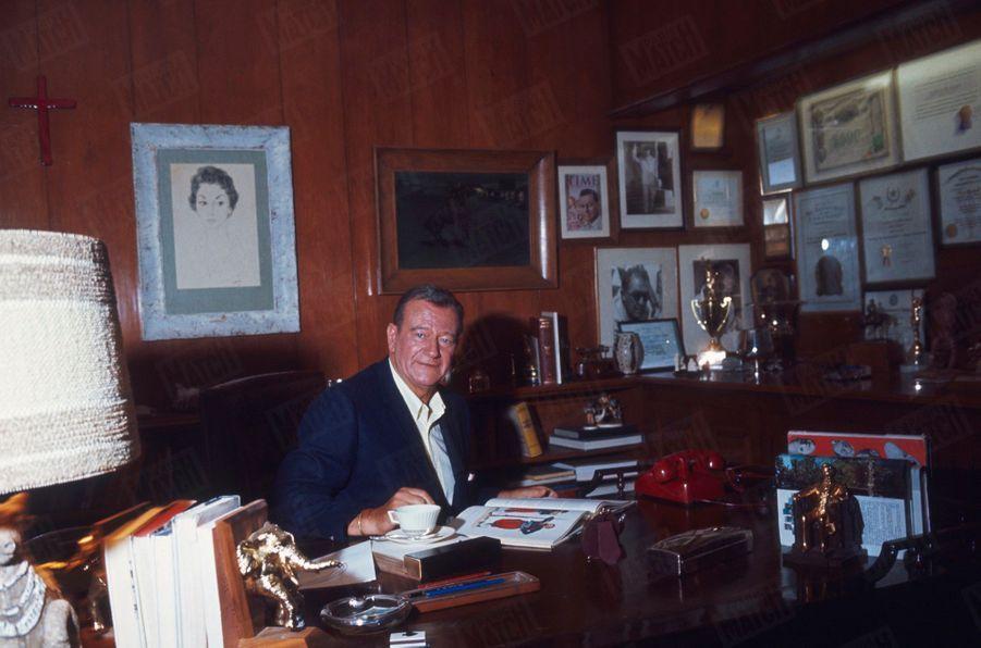 John Wayne dans le bureau de sa villa, à Newport Beach, Californie, en juin 1967. Au mur, parmi ses plus beaux trophées, une photo dédicacée d'Eisenhower.