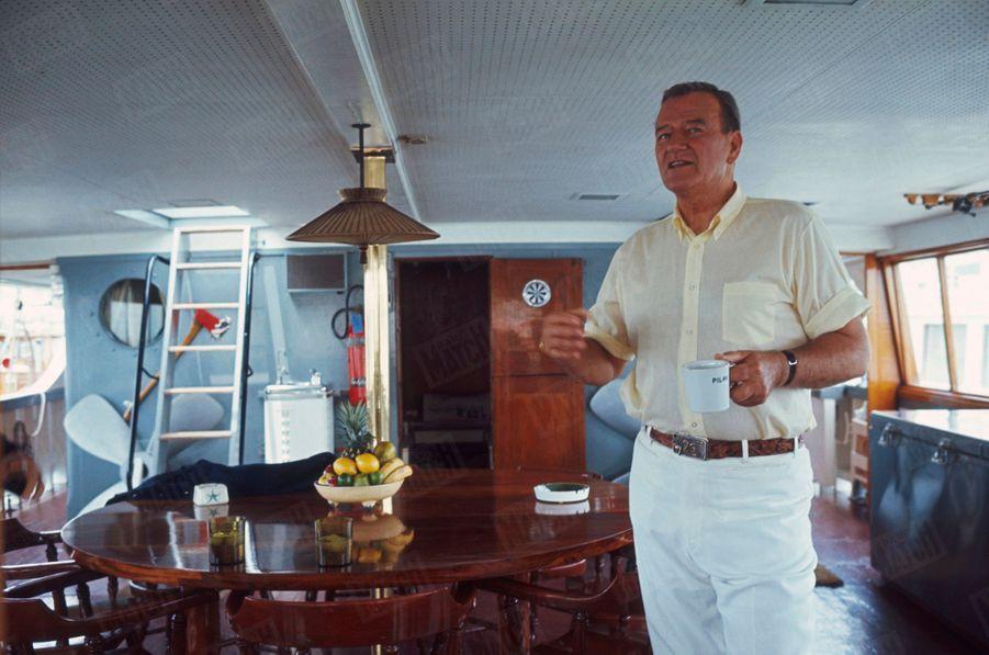 """« John Wayne en pantalon blanc de """"captain"""" a bord de son yacht de quarante-cinq mètres l'""""Oie sauvage"""", un ancien dragueur de mines. Depuis son opération, Wayne ne boit plus que du café, dans des tasses marquées au prénom de sa femme. » - Paris Match n°951, 1er juillet 1967."""