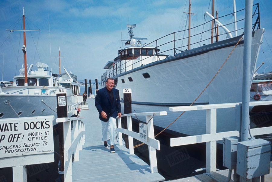 """John Wayne à côté de son yacht de quarante cinq mètres, """"The Wild Goose"""" (l'Oie sauvage), un ancien dragueur de mines, à Newport Beach, Californie, en juin 1967."""