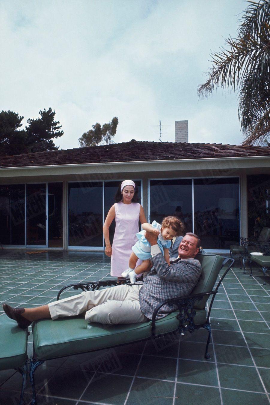 """« """"L'Homme tranquille"""", sur la terrasse de sa maison de Newport. A ses côtés, sa femme Pilar, une comédienne péruvienne, et la dernière-née de ses sept enfants : Marisa, quinze mois. » - Paris Match n°951, 1er juillet 1967."""