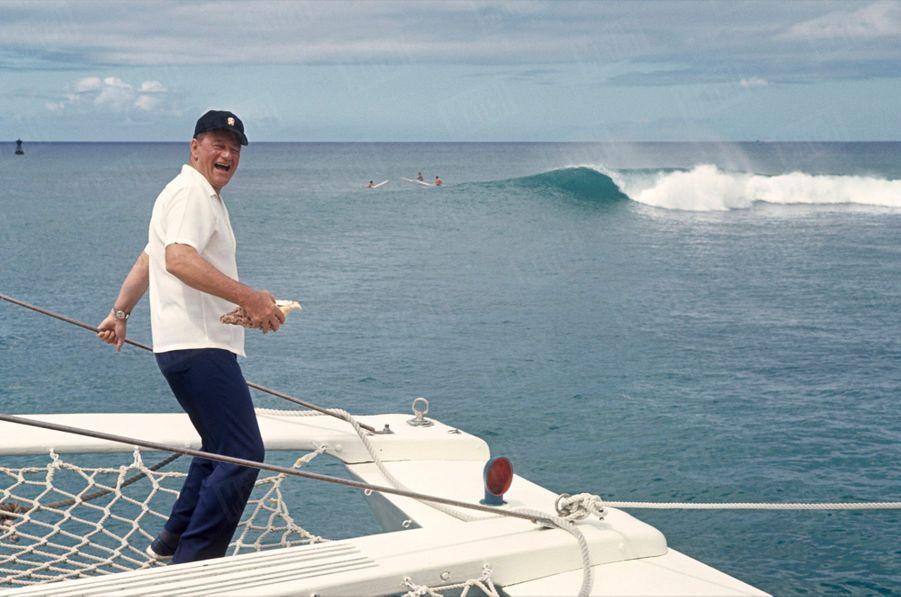 """John Wayne debout à l'arrière de son yacht """"The Wild Goose"""" (l'Oie sauvage), à Newport Beach, Californie, en juin 1967."""
