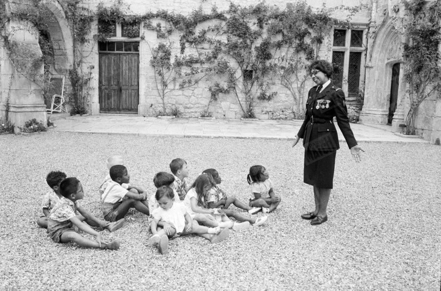 Joséphine Baker reçoit la Légion d'Honneur et la Croix de guerre, entourée de ses enfants au Château des Milandes, en août 1961.