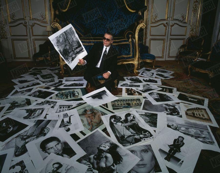 Karl Lagerfeld posant chez lui au milieu de quelques unes de ses photos préférées, à l'occasion d'une exposition de ses clichés à la Galerie Boulakia, à Paris, en janvier 1991.
