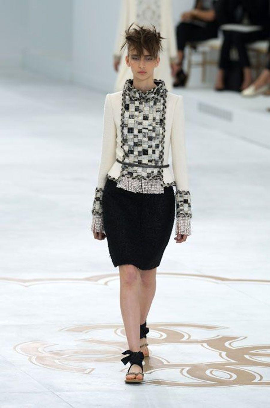 Sous la grande verrière du Grand Palais, KarlLagerfeld a présenté la collection automne-hiver de Chanel, mardi. Dans un décors épuré et blanc hivernal, les silhouettes des mannequins se sont fait sages. Les cols sont sont hauts, les broderies abondantes, les manches longues protègent les bras de la rigueur du froid, et l'extravagance n'est pas de mise pour les modèles de robes et de jupes, rarement au-dessus du genou et dans les tons noir, blanc, rouge, or ou bleu. Les tailleurs en tweed ont traditionnellement débuté l'événement, et pour la clôture, le créateur allemand a invitéun mannequin enceinte pour revêtir la robe de mariée Chanel, à la longue traîne et à l'inspiration plutôt baroque.