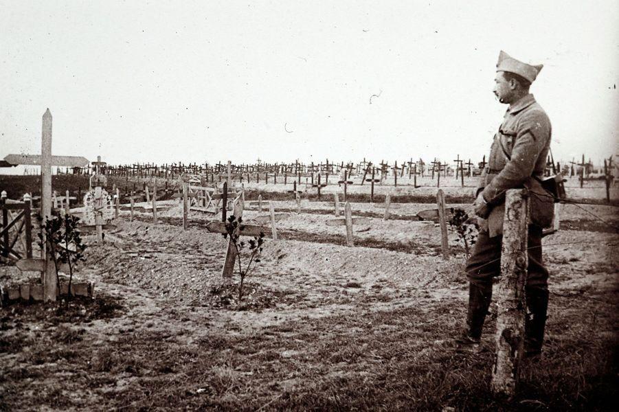 Un officier français se tient devant les tombes fraîches de soldats tombés au combat, àSaint-Jean-sur-Tourbe, sur le front de Champagne.
