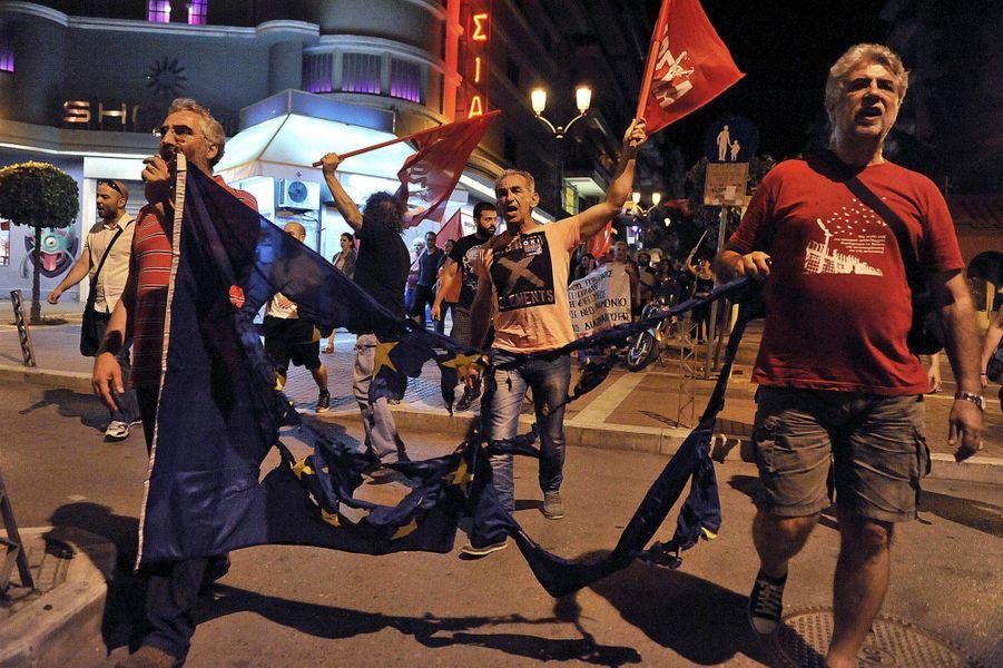 """Dans les rues de Thessalonique, des partisans du """"non"""" brûlent un drapeau de l'Union Européenne."""