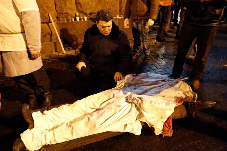 Un homme tient la main de son fils tué dans la répression d'une manifestation