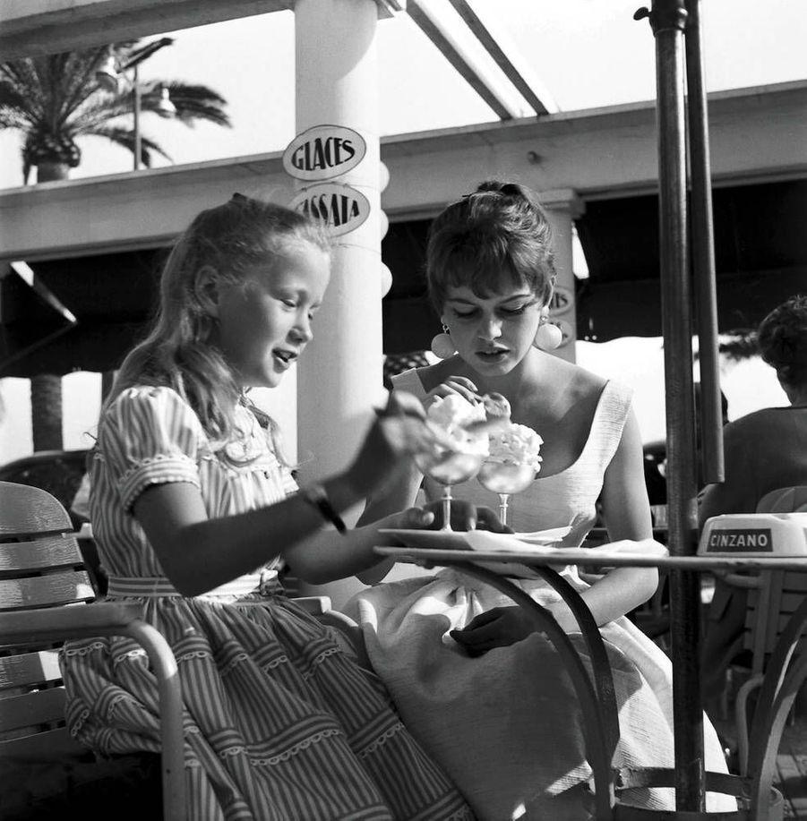 Pause gourmande pour Brigitte Fossey et Brigitte Bardot, au 8e Festival de Cannes. 1955.