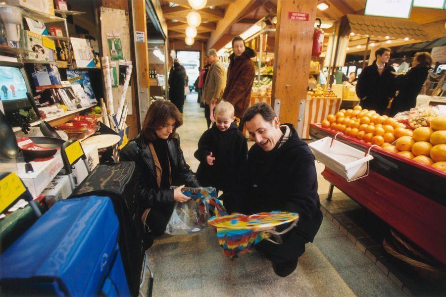 Nicolas SARKOZY et son ex-épouse Cécilia faisant leur marché à Neuilly-sur-Seine : accroupis dans une allée du marché couvert, le maire de Neuilly et Cécilia déballant un cerf-volant pour l'offrir à leur fils Louis impatient de voir son cadeau