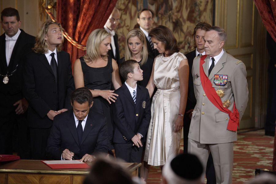Mercredi 16 mai 2007 à l'Elysée, cérémonie d'investiture de Nicolas Sarkozy à la présidence de la République. Dans la salle des Fêtes où se déroule la cérémonie de passation des pouvoirs, le nouveau président signant un document, sa famille debout derrière lui, avec le petit dernier Louis (10 ans).