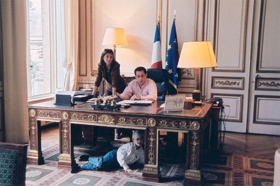 Nicolas Sarkozy, nouveau ministre de l'Intérieur, à son bureau de la place Beauvau à Paris : Cécilia debout au côté de son ex-époux, leur fils Louis, 5 ans, jouant sous le bureau, dans un remake de John John.
