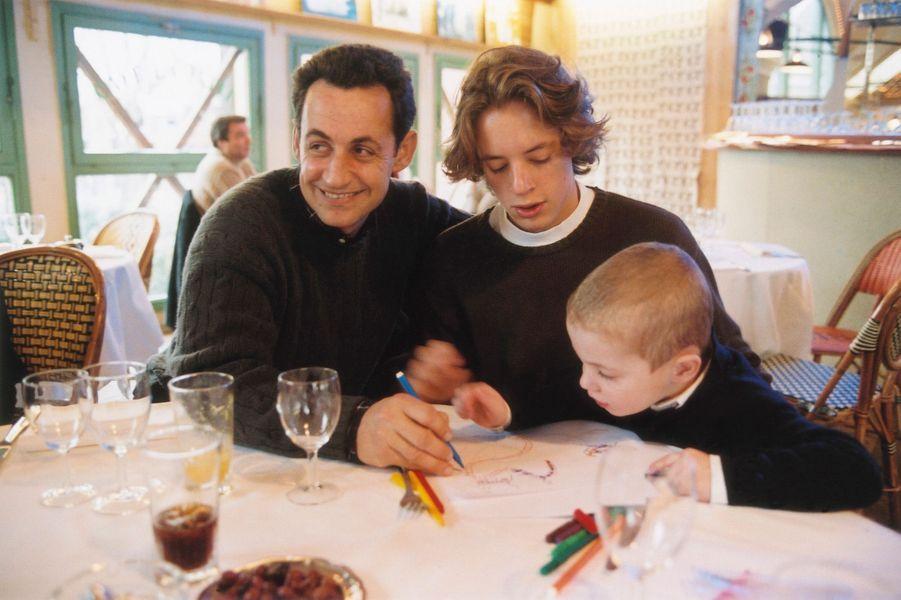 Le député-maire de Neuilly Nicolas Sarkozy déjeunant en famille au café de la Jatte à NEUILLY-SUR-SEINE : le maire dessinant pour son fils cadet Louis (3 ans) sous l'oeil de son aîné Pierre (16 ans).