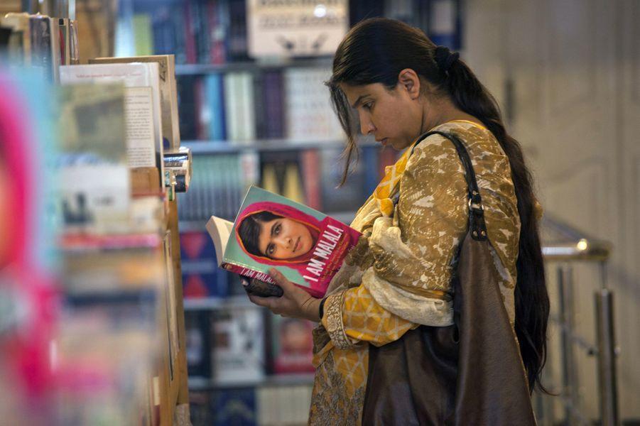 Une femme feuillette le livre de Malala dans une librairie d'Islamabad, au Pakistan, le 8 octobre 2013