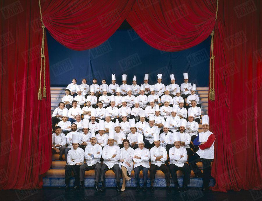 En 1984, une soixantaine de chefs réunis pour honorer Bernard Loiseau, Grand Prix Hachette des cuisiniers. Au premier rang, à gauche, entre Joël Robuchon et Paul Bocuse, Marc Meneau.