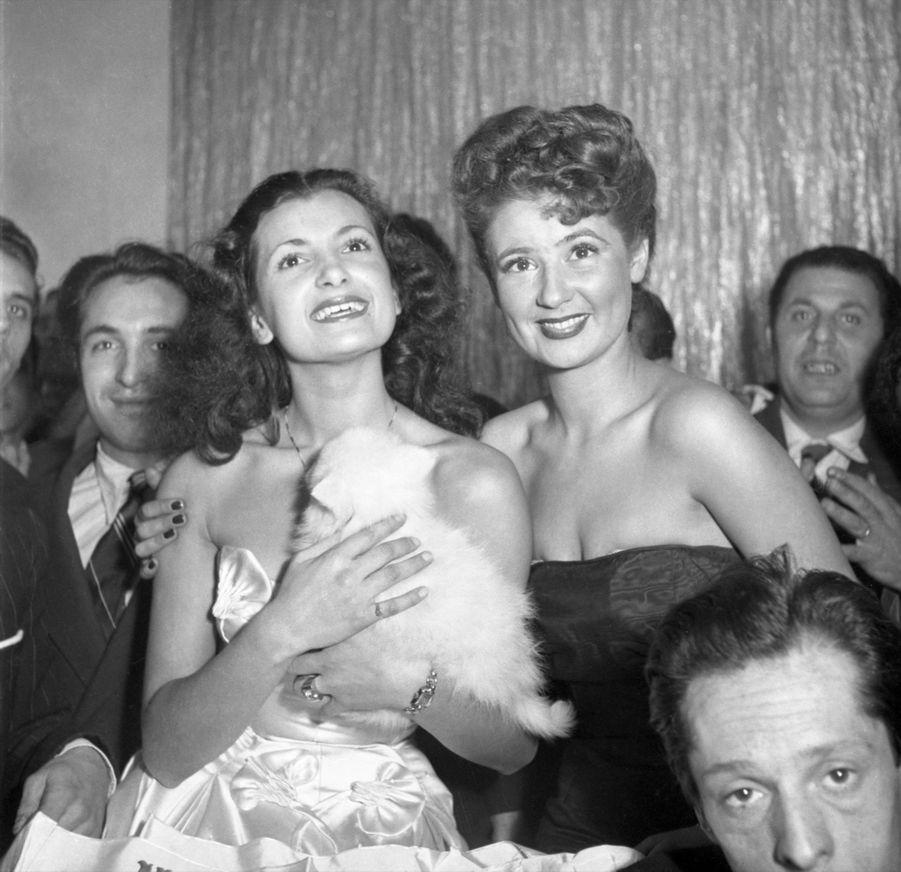 """Juliette Figueras, Miss France 1949 (en robe blanche), en compagnie de sa première dauphine Colette Deréa, le soir de son élection, le 21 décembre 1948, au cabaret """"Le Tyrol"""", à Paris."""