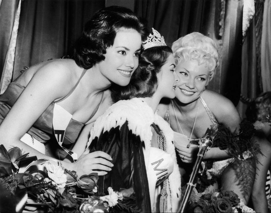 Claudine Auger (à g.) pose avec Miss Monde 1958, la Sud-Africaine Penelope Coelen dont elle a été désignée la 1ère Dauphine, à l'issue du concours qui s'est tenu à Londres le 13 octobre 1958. À droite, la 2ème Dauphine, la Danoise Vinnie Ingemann.